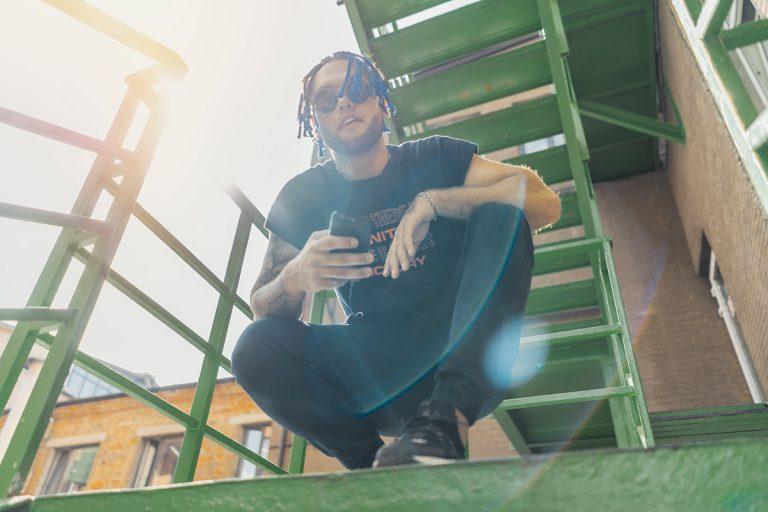 Reggaetonero sentado en escaleras